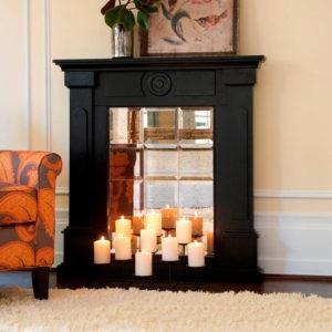 czarny kominek z lustrzanymi kafelkami i świecami