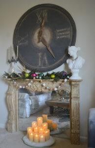 rustykalny sztuczny kominek z lustrzanym tłem i świeczkami różnej wielkości